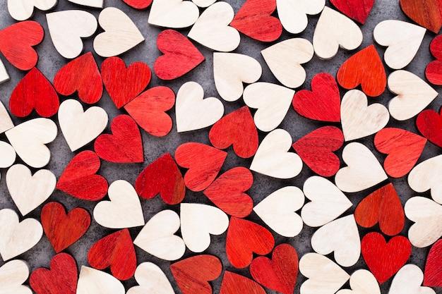 Белые и красные сердца, фон с деревянными сердечками.
