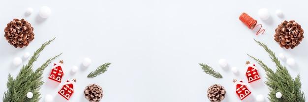 크리스마스 트리 분기, 빨간색 장식, 선물 상자 및 원뿔, 평평한 위치, 복사 공간, 웹 배너가 있는 흰색 및 빨간색 최소 크리스마스 테두리 웹 배너