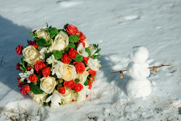 雪の中で白と赤のバラのウェディングブーケと雪だるまの結婚指輪。冬の結婚式