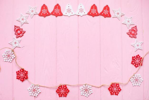 白と赤の星とクリスマスツリーがピンクの木の表面にフレーム
