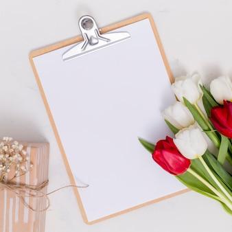 白と赤のチューリップの花。ギフト用の箱;空白のホワイトペーパークリップボードと白い背景で隔離