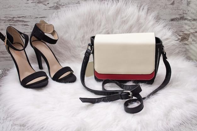 白と赤の女性のバッグ、白い毛皮の黒い靴。ファッショナブルなコンセプト