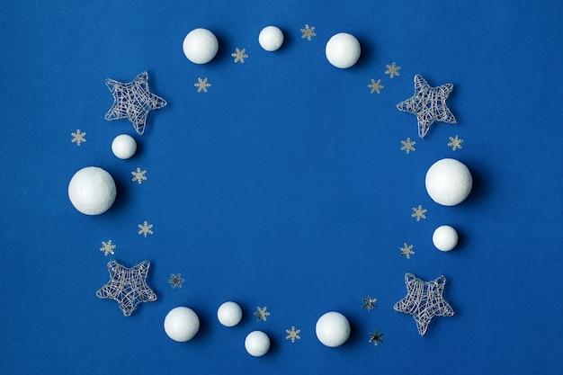 白と銀の装飾は、コピースペースのある古典的な青い背景の上に平らに置かれました。スタイリッシュな白と銀の装飾品、上面図とクラシックブルーの色のクリスマスの背景