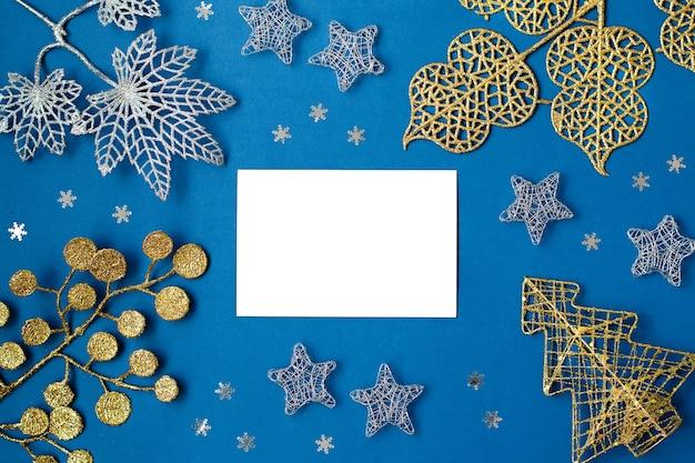 白と銀の装飾は、コピースペースのある古典的な青い背景の上に平らに置かれました。白と銀の装飾品とクラシックブルーの色のクリスマスの背景、ウィッシュリストとクリスマスの背景