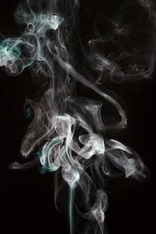 검은 배경에 고립 된 흰색과 청록색 보라색 연기 파도