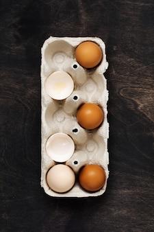 古い暗い木製の古いセルロースヴィンテージコンテナ内の白と黄色の鶏の卵と殻