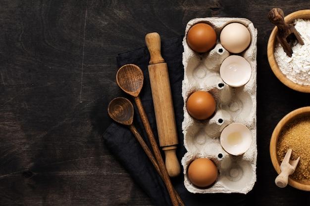 밀가루, 설탕, 나무 숟가락과 오래 된 어두운 나무에 롤링 핀이있는 오래된 셀룰로오스 빈티지 용기에 흰색과 노란색 닭고기 달걀과 껍질 프리미엄 사진