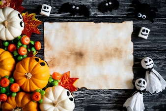 White and yellow ghost pumpkins with Autumn leaves and old paper on a black wooden backgro