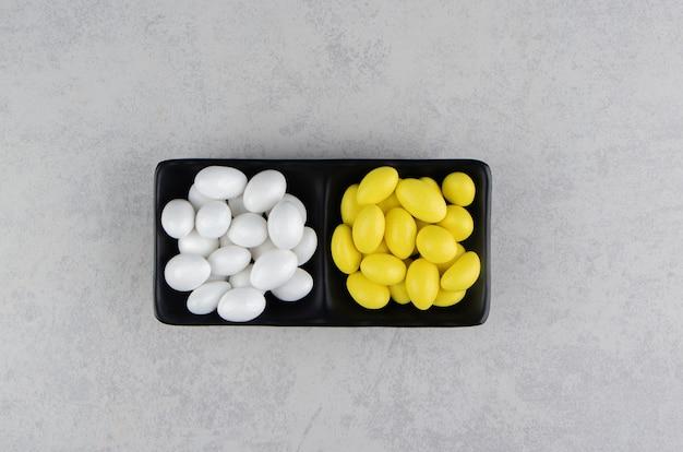 大理石の表面のトレイにある白と黄色のガム