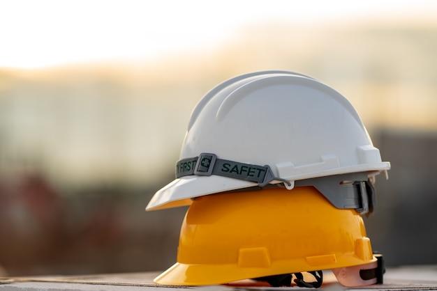 Безопасность каски белого и желтого шлема при строительстве площадки, безопасность концепции прежде всего.