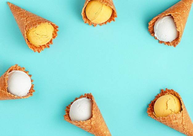 Белые и желтые рожки мороженого на ярко-синем фоне. застелить tflat, скопировать пространство.