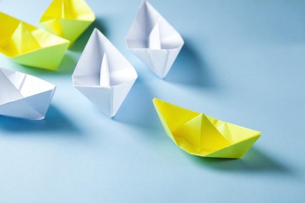 Белые и желтые бумажные кораблики на синей поверхности