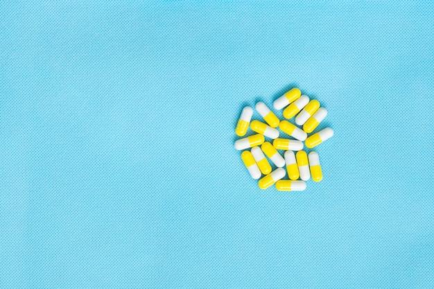 白と黄色の錠剤は、青色の背景にコピースペースを備えた医薬品コンテンツのフラットレイを設定します。ビタミンサプリメントの上面図。医療の概念。