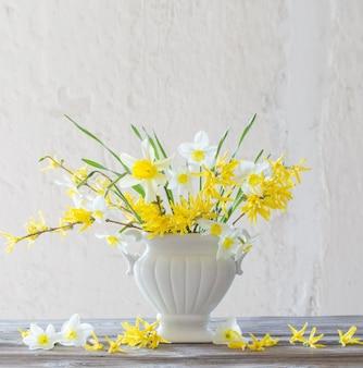 表面の古い白い壁の花瓶に白と黄色の春の花