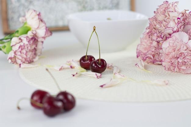 Белый ангел на столе. красивые розовые цветы на белом столе.