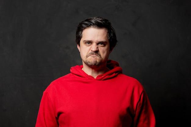 Белый злой парень в красной толстовке на темной стене