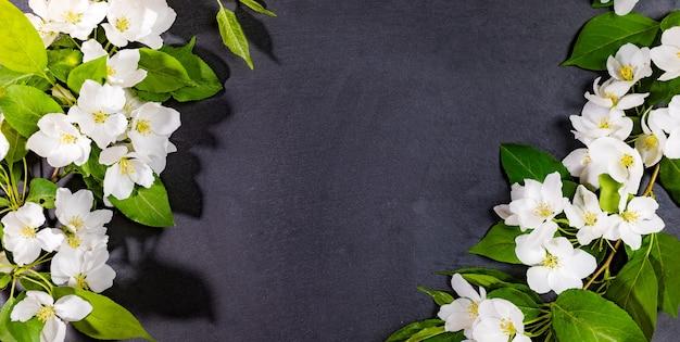 Белые ветви яблони на пустой сланцевой черной сервировочной доске. праздничный макет для сервировки или рецептов на весенние праздники. вид сверху, копия пространства.
