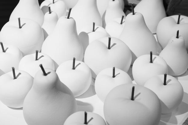 Белые яблоки и груши из гипса в магазине товары для покраски и продажи.
