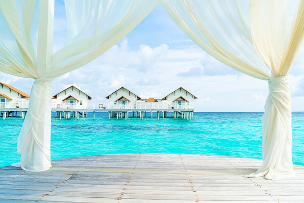 White arch with tropical maldives resort and sea
