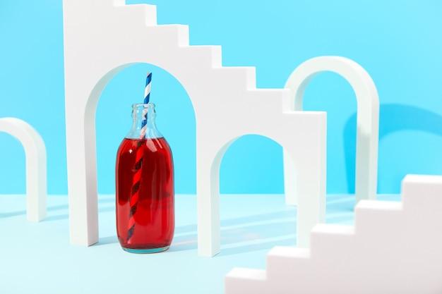 ボトルにクランベリー レモネード カクテルを使用した青色の背景に白いアーチのクリエイティブな構成