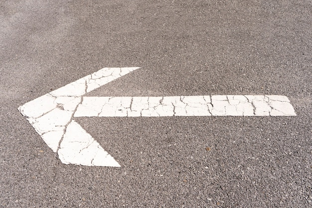 White arrow on the asphalt floor of a parking lot to direct traffic.