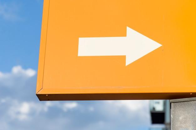 White arrow on orange background