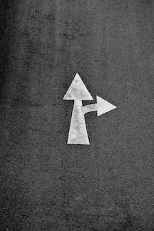 White arrow painted on asphalt road (go straight and turn right)