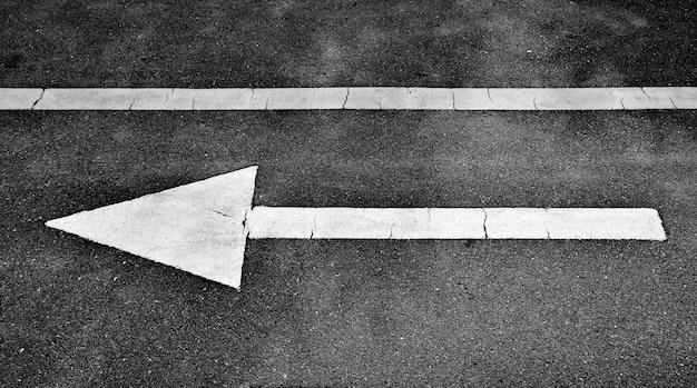 White arrow painted on asphalt road