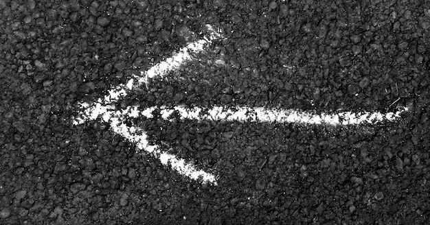 White arrow painted on asphalt road