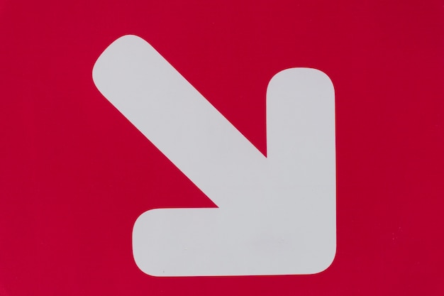 White arrow on red background