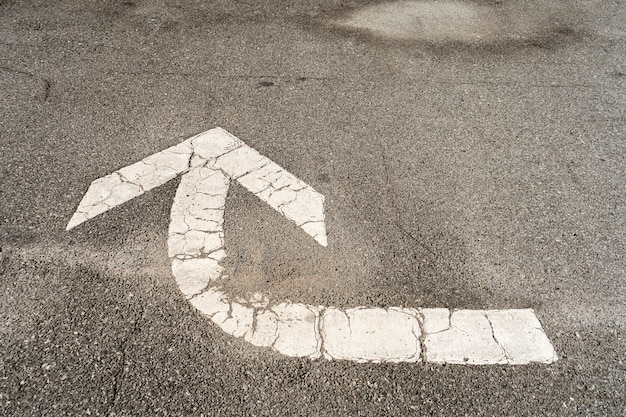White arrow that indicates that it is necessary to turn engraved in the asphalt floor of a parking lot to direct the traffic.