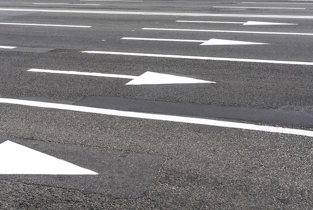 アスファルト道路と都市インフラの白い矢印道路標示