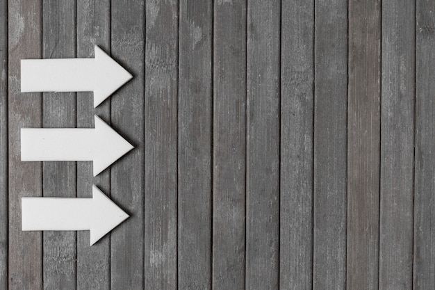 White arrows on wooden background