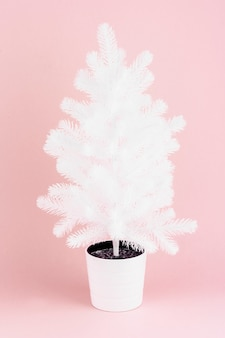 White artificial christmas tree on pink background