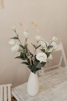 花瓶に白い造花。テーブルの上の装飾的な花。インテリアの花。
