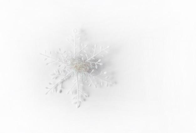 白い人工雪片。白い背景の上のクリスマスや新年の装飾。