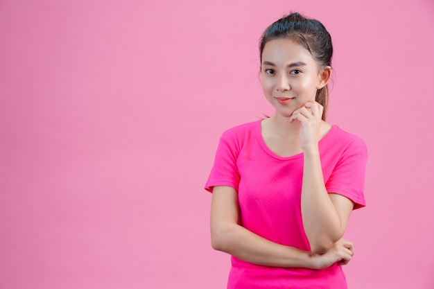 White asian women wear pink shirts. put his left hand in his face on the pink .