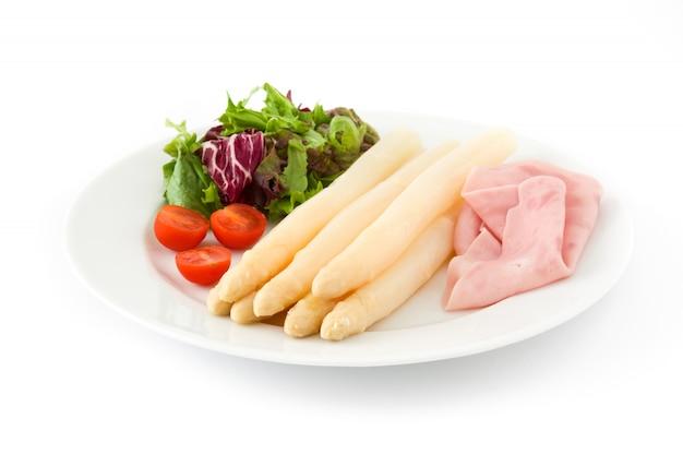 Белая спаржа с салатом и ветчиной на белом