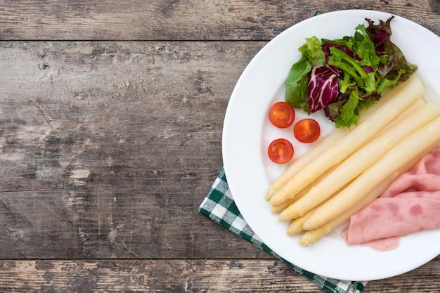 Белая спаржа с салатом и ветчиной на деревянный стол копией пространства