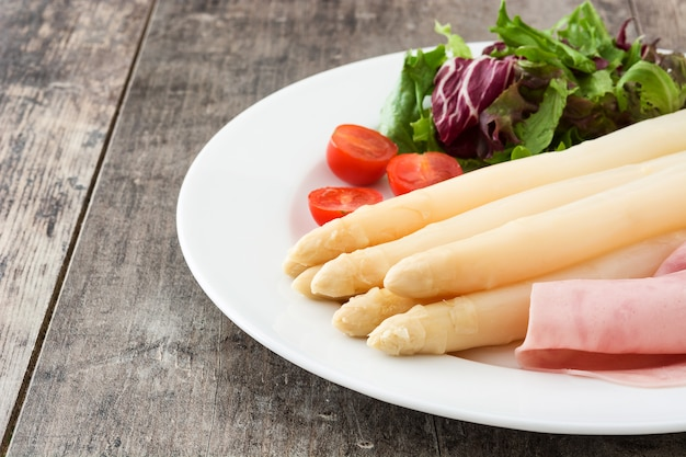 Белая спаржа с салатом и ветчиной на деревянный стол