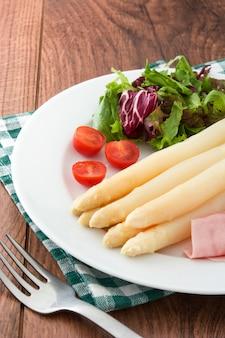 Белая спаржа с салатом и ветчиной на деревянном