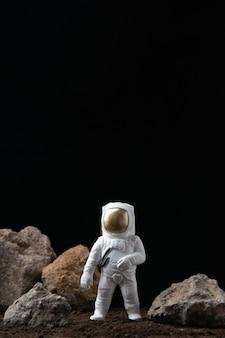 어두운 공상 과학 판타지에 바위와 달에 흰색 우주 비행사