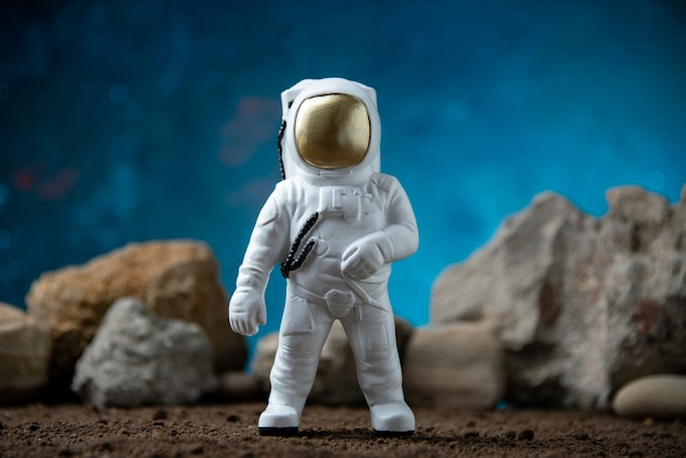 White astronaut with rocks on a moon blue  fantasy cosmic sci fi