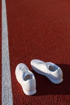 スタジアムのトレッドミルにある白いアスレチックスニーカー。スポーツ、健康、ウェルネスの概念。