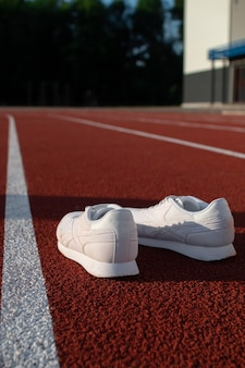 White athletic sneakers on a stadium treadmill. concepts of sport, health and wellness.