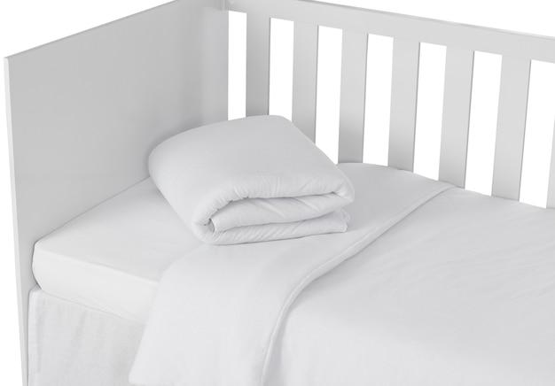 Белая детская кроватка, изолированных на белом фоне. деталь пухового одеяла.
