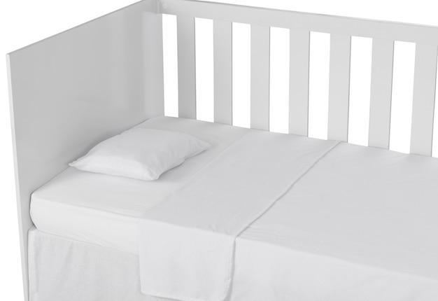 Белая детская кроватка, изолированные с подушкой и пуховым одеялом на белом фоне. детальный вид.