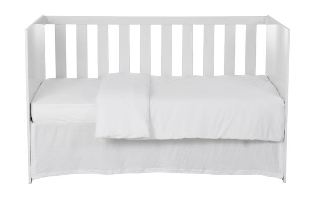 Белая детская кроватка с пуховым одеялом на белом фоне.