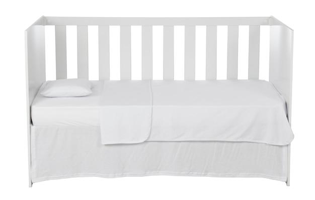 Белая детская кроватка с подушкой и пуховым одеялом на белом фоне.