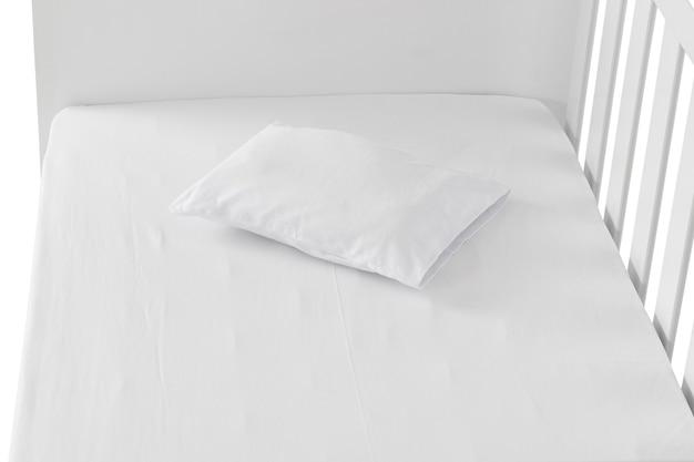 Белая детская кроватка с деталью подушки изолированной на белой предпосылке.